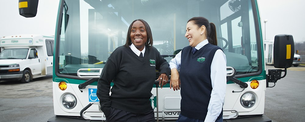 A DRT supervisor and operator in front of a bus