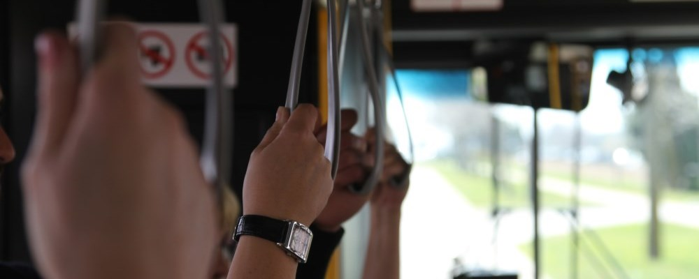 People holding the hand straps on a bus